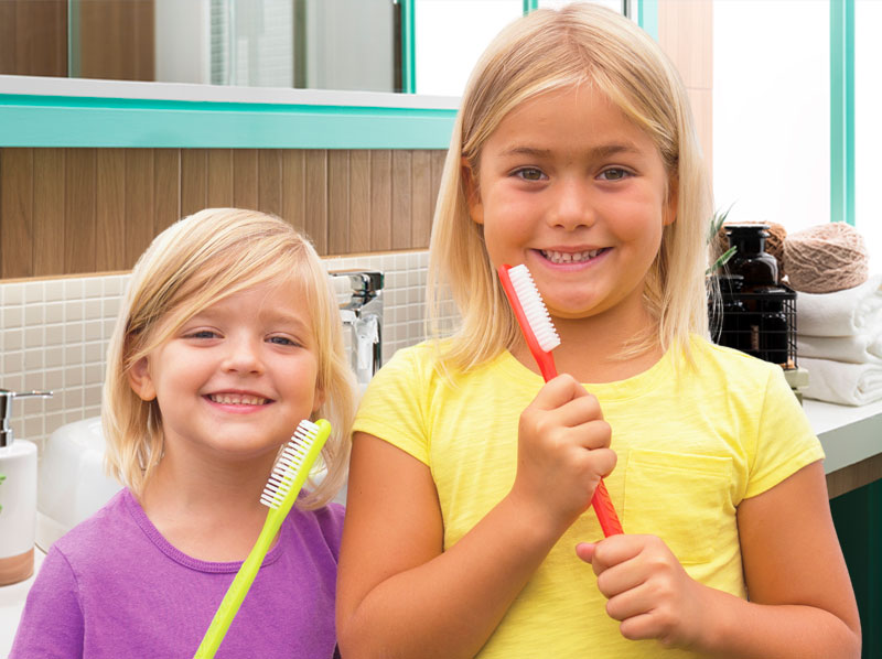 Two young girls in a bathroom holding giant toothbrushes.